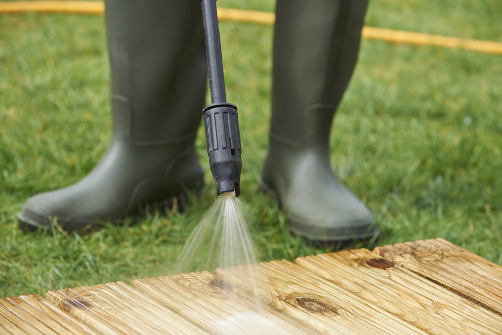 Man Washing Wooden Decking With Pressure Washer